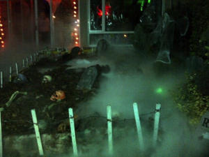 A front garden decorated with Halloween props to look like a graveyard with Halloween dry ice fog and LED lights.