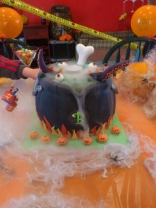 A cake that looks like a Halloween witch's cauldron with Halloween dry ice fog flowing from it.